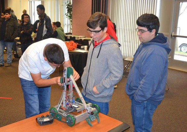 Conor Shortnacy, Phillip Augusto and Anthony Augusto prepare their robot.