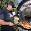 Steve Gonzalez of Fatte Alberts Pizza takes a pie from the oven during the Central Valley Pizza Festival on Sunday.