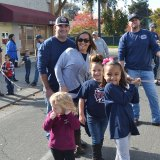Fireman Matt Moreno, spouse Kirby, and daughter Mayce join Kiani Shiyomura and Charlee Areies in raising the tree.