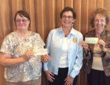 Charlotte Meade, Rotary President (center), presents check to Alice Quezada, vice president, and Wilma Humason, treasurer (far right), friends of the Kings County Library.