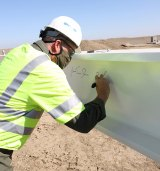 "NAS Lemoore Commanding Officer Doug Peterson signs a beam during a ""topping out"" ceremony at the half-way point of construction on a new F 35C Lightning II hangar."