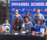 Immanuel High School standout football player Winston Williams (center), flanked by friends and family, signs a letter-of-intent to attend UC Davis to play football.