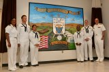 Capt. Kristen Atterbury and Navy Surgeon Vice Adm. General C. Forrest Faison join the navy artist who painted a mural commemorating the 50th anniversary of the hospital/clinic Thursday morning.