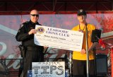 Sergeant Jim Chaney accepts a $1,000 check from Lemoore Lions on behalf of the Police Activities League.