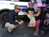 A Lemoore officer greets a National Night Out enthusiast as Tanglewoood Apartments.