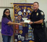 Officer Kevin Cosper accepts a donation from Lemoore Lions Club President Ever Casas.