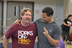 Kent Olson, left, shares a moment with former Tiger state wrestling champ and college national champion Chris Pendleton during a local basketball camp. Olson is the new head coach at Dinuba High School.
