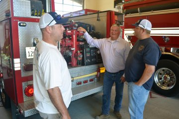 Lemoore firefighters are always on the job. Here, Sterling Stinger (left) and Stuart Lyons (right) confer with Fire Chief Bruce German.