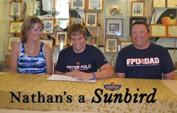 Nathan Olson, with Mom Heather and Dad Nathan at his signing ceremony.