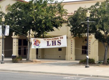 "A welcome to Lemoore High School banner oversees an empty Lemoore High School student parking lot. School officials are scratching their heads over a recent ""probation"" accreditation."