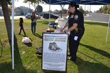 Lemoore PD Commander, Margaret Ochoa helps out at the annual Shoe Drive.