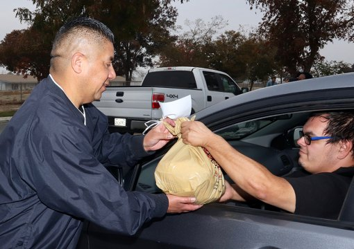 Kings County Supervisor Richard Valle helps distribute turkeys during Operation Gobble Turkey Giveaway Monday afternoon in Hanford's Home Garden area.
