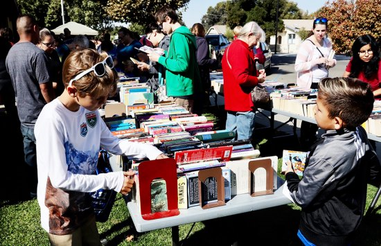 Local book enthusiasts, including these two youths, look for good reads at Saturday's (Oct. 12) Bi-annual Kings County Book Sale held at the Lemoore Library.
