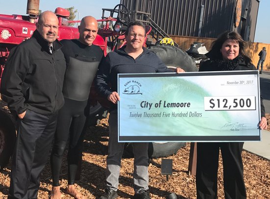 Surfing legend Kelly Slater (second from left) presents a $12,500 check to city officials, including Mayor Ray Madrigal, City Manager Nathan Olsen, and Community Development Director Judy Holwell.