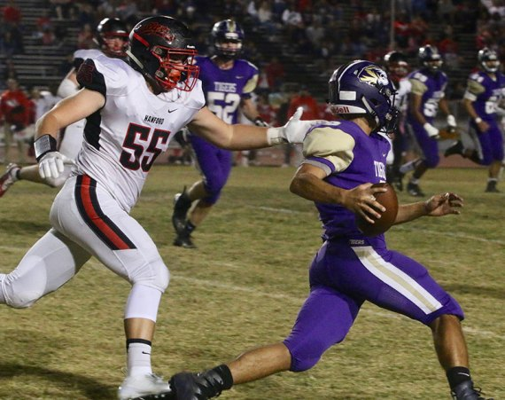 Lemoore's Noah Gonzalez looks for an opening as Hanford's Mason Brosseau gives chase Friday night in Tiger Stadium. The Tigers ended their season with a 42-6 loss to Hanford.
