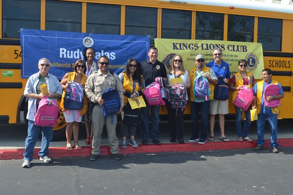 "Assembly Member Rudy Salas joins Kings Lions Club members and others at the annual ""Stuff the Bus"" event Saturday at the Lemoore Kmart."